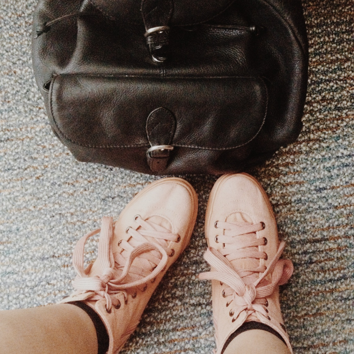 pink studded sneakers and leather backpack